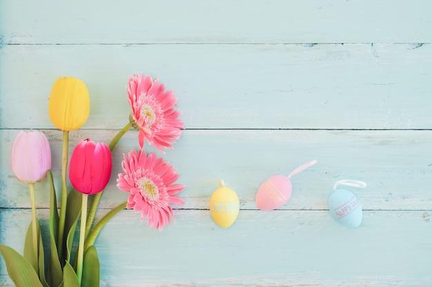 素朴な木の板の背景にチューリップの花とカラフルなイースターエッグ。