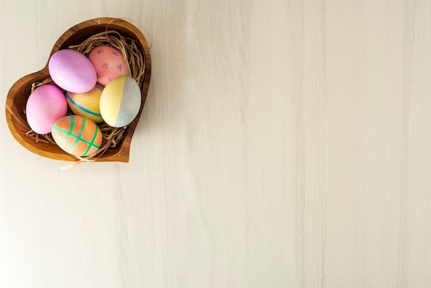 Colorful easter eggs in wooden plate on gray table with place for text, top view