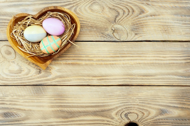 Colorful easter eggs in a wooden plate on a wooden surface with place for text, top view