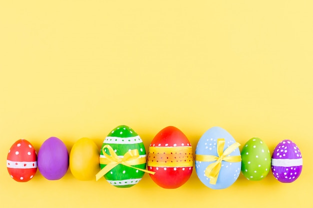 Colorful easter eggs on yellow background flat lay. copy space, top view