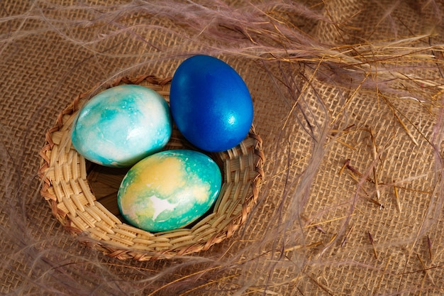 갈색 천 배경에 다채로운 부활절 달걀 노란색 파란색과 파란색 색상