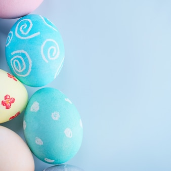 Colorful easter hunting eggs dyed by colored water with beautiful pattern on pastel blue background, design concept of holiday, top view, copy space.