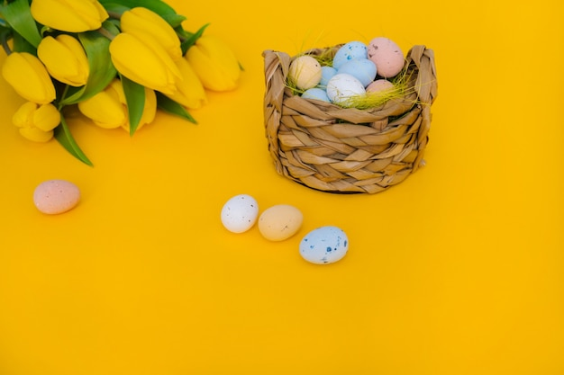Colorful easter painted speckled eggs in basket with yellow tulip flowers