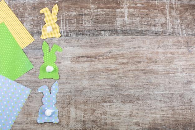 Красочные пасхальные бумажные кролики с хвостом на деревянном столе