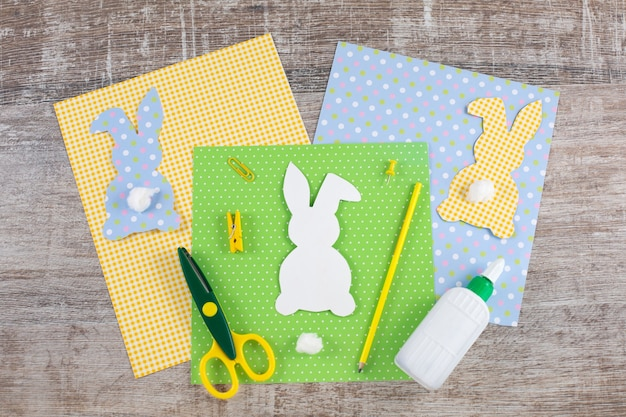 Colorful easter paper bunnys rabbits with a tail on wooden table