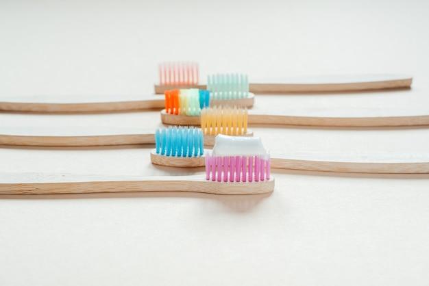 明るいパステルカラーの背景にカラフルな環境にやさしい竹の歯ブラシ、ゼロウェイストコンセプトの歯科治療、持続可能なライフスタイル