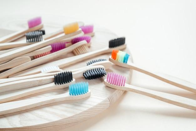 Красочные экологически чистые зубные щетки из бамбука на деревянном подносе, уход за зубами без отходов, экологичный образ жизни