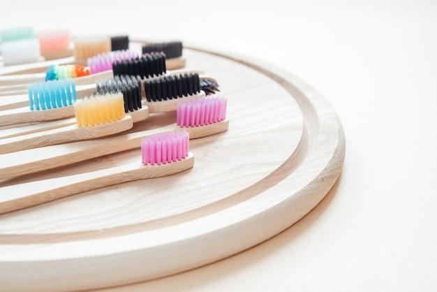 木製トレイのカラフルな環境に優しい竹の歯ブラシ、ゼロウェイストコンセプトの歯科治療、持続可能なライフスタイル