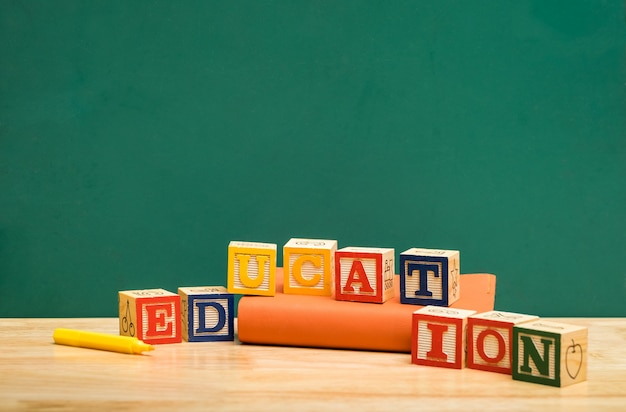 Colorful education word wood block on book with pen on wood table with green blackboard