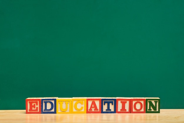 Colorful education word wood block on wood table with green blackboard