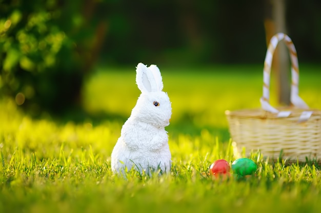 Colorful eggs and cute white toy bunny during egg hunt on easter