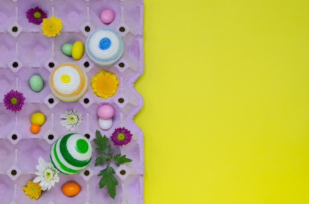 Colorful eggs decorate with knitting wool for easter day and festival put in purple egg tray.