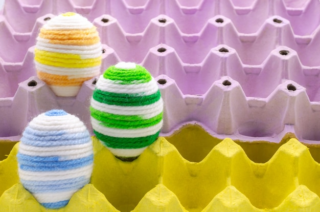Colorful eggs decorate with knitting wool for easter day.