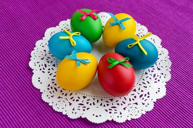 鮮やかな背景に白いナプキンに休日イースターのためのカラフルな卵。