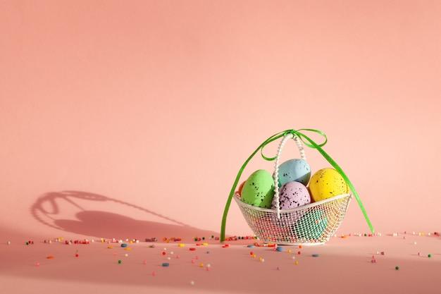 ピンクの背景に朝日光とバスケットのカラフルな卵。コンセプトイースター。
