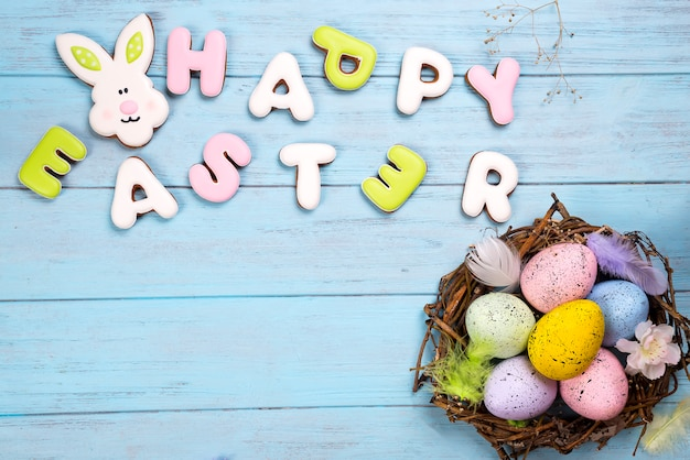 Colorful eggs in nest on blue wooden background and cookies lettering happy easter