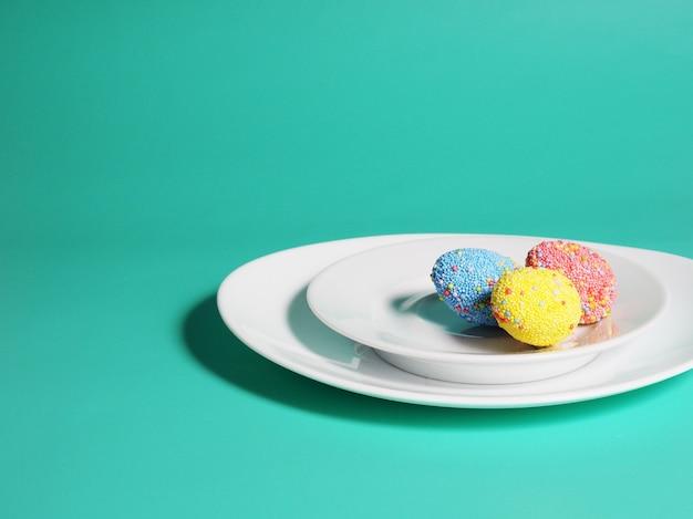 Красочные яйца на тарелке, ярко-зеленый синий фон, концепция пасхи.