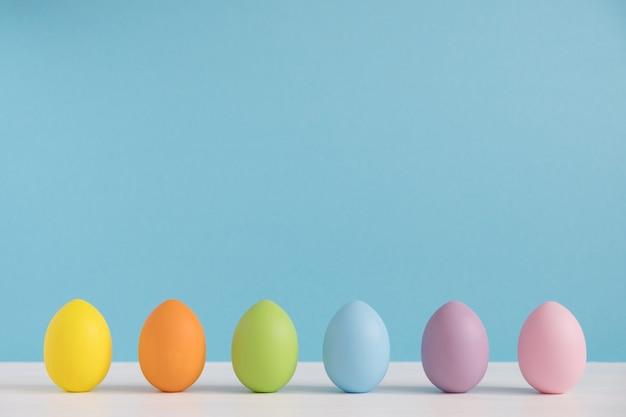 水色の背景にカラフルな卵。ハッピーイースターの背景。最小限のイースター。レインボーカラー