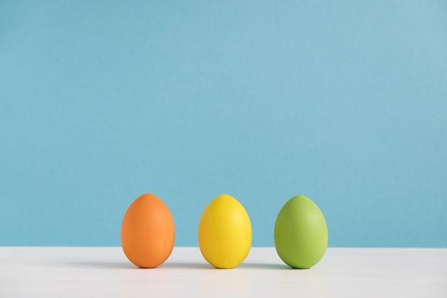 밝은 파란색 벽에 다채로운 계란입니다. 행복한 부활절. 최소한의 부활절.
