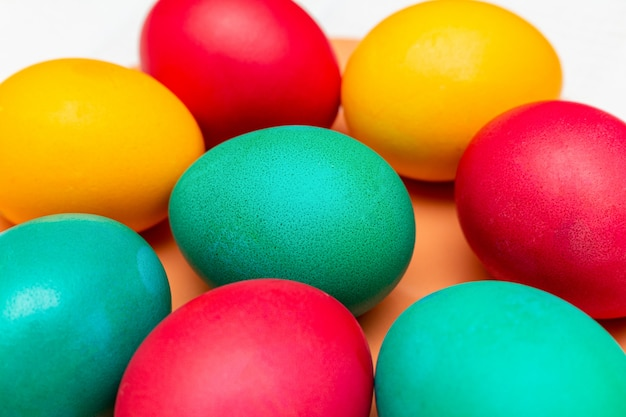 Colorful eggs on the orange dish for the easter close up