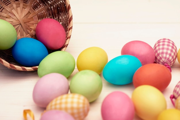 Colorful eggs scattering from a wicker bowl