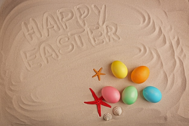 Colorful eggs and text happy easter written on sand