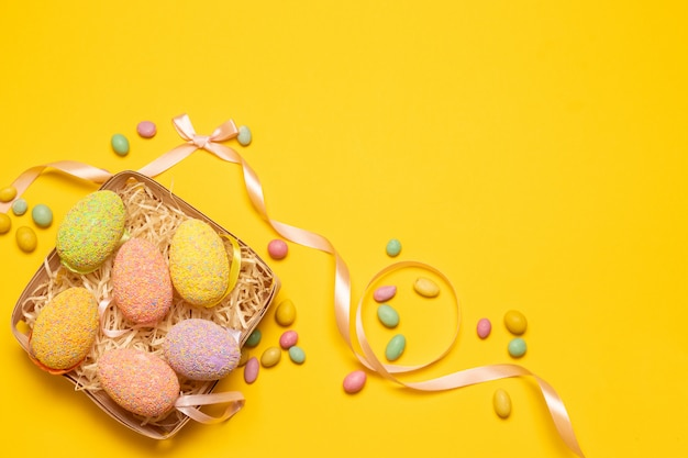 Colorful eggs in a wicker basket with colored decorations on a yellow background