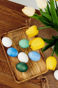 Colorful eggs on a wooden tray flowers easter holiday