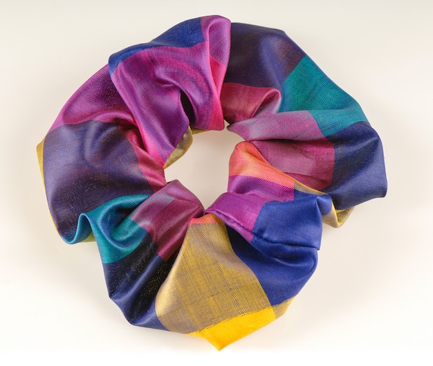 Colorful elastic band for hair on white background top view