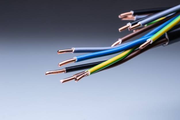 구리 배선이 분리된 회색 배경에서 끝나는 다채로운 전기 케이블.
