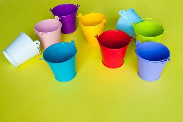 Colorful empty buckets on yellow background