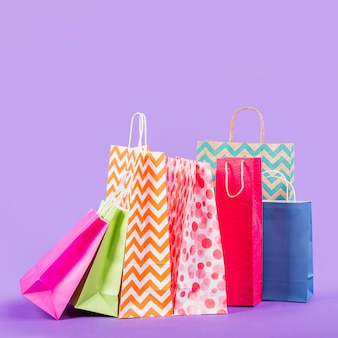 Colorful empty shopping bags on purple background