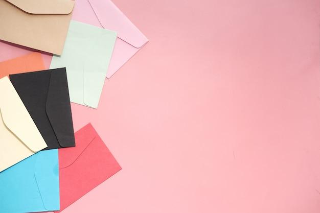 Красочный конверт на розовом фоне с копией пространства.