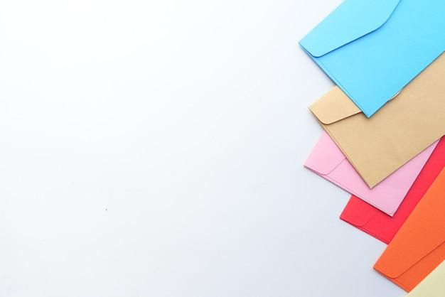コピースペースと白い背景の上のカラフルな封筒。