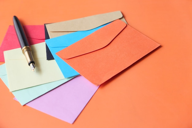 Красочные конверты и перьевая ручка на оранжевом фоне.