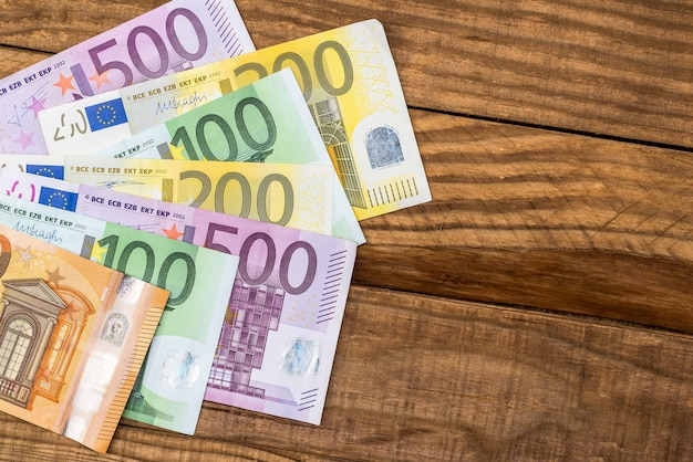 Colorful euro banknotes on wooden desk background