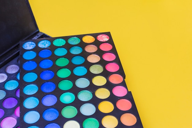 Colorful eye shadow palette on yellow background