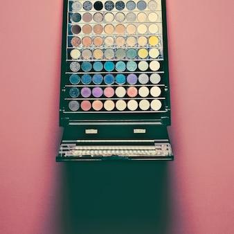 Палитра красочных теней для век. макияж ванильный розовый фон