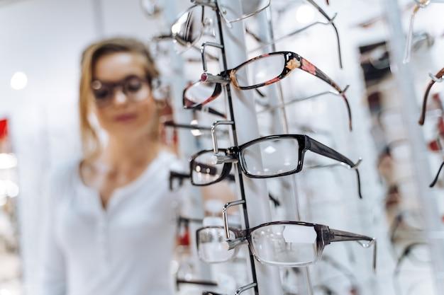 현대적인 모양의 다채로운 안경테가 연속으로 있습니다. 안경점. 안경점에서 안경을 쓰고 서십시오.