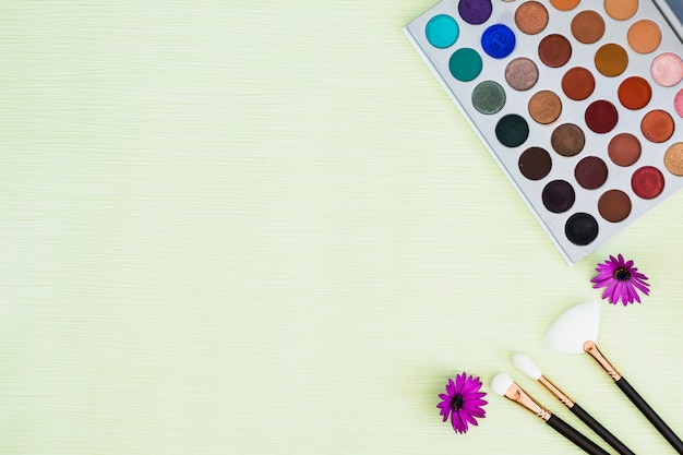 Colorful eyeshadow palette with purple flower and makeup brushes on mint background