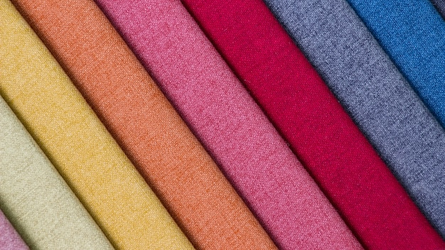 Разноцветные ткани, стопка разноцветных тканей.