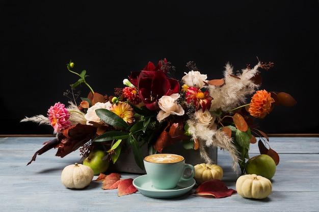나무 테이블에 화려한가 꽃다발입니다. 커피 컵, 호박, 장미, 튤립, 달리아, 마른 잎과 허브의 가을 구성.