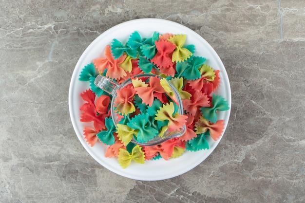 Pasta farfalle colorate in tazza di vetro.