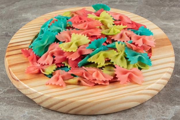 Красочная паста фарфалле на деревянной тарелке