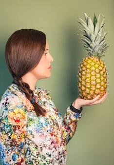 緑の背景の上に彼女の手でパイナップルを探しているカラフルなファッションの女の子の肖像画