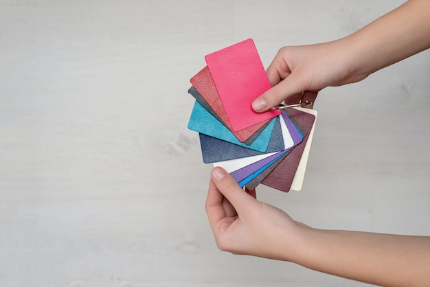 Colorful fashion samples made of genuine leather in the hands of the designer, modern stores, industry concept. palette catalog with color leather samples.