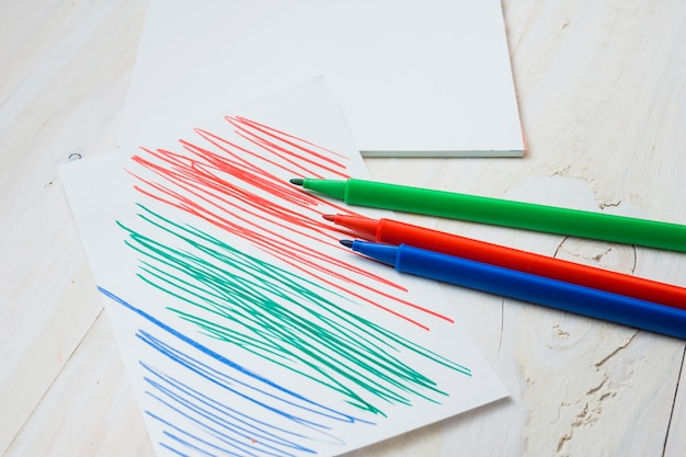 Colorful felt tip pen and paper with pen stroke on white wooden table