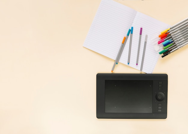 Colorful felt-tip pens on notebook with graphic digital tablet over colored background