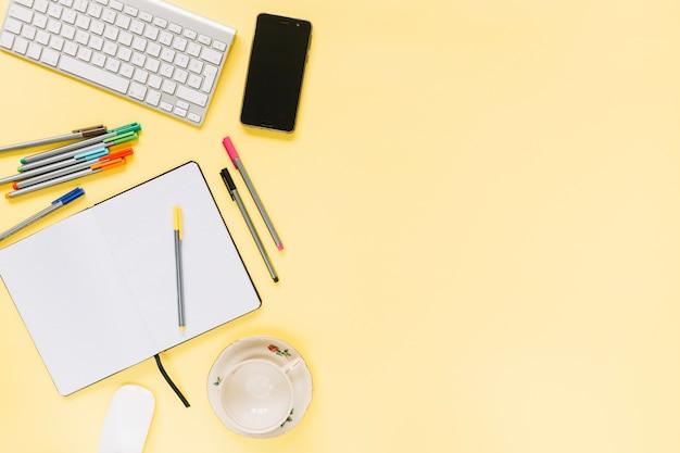 Цветные фломастеры; ноутбук с клавиатурой и сотовый телефон на желтом фоне