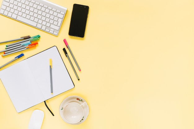 Colorful felt-tip pens; notebook with keyboard and cellphone on yellow background